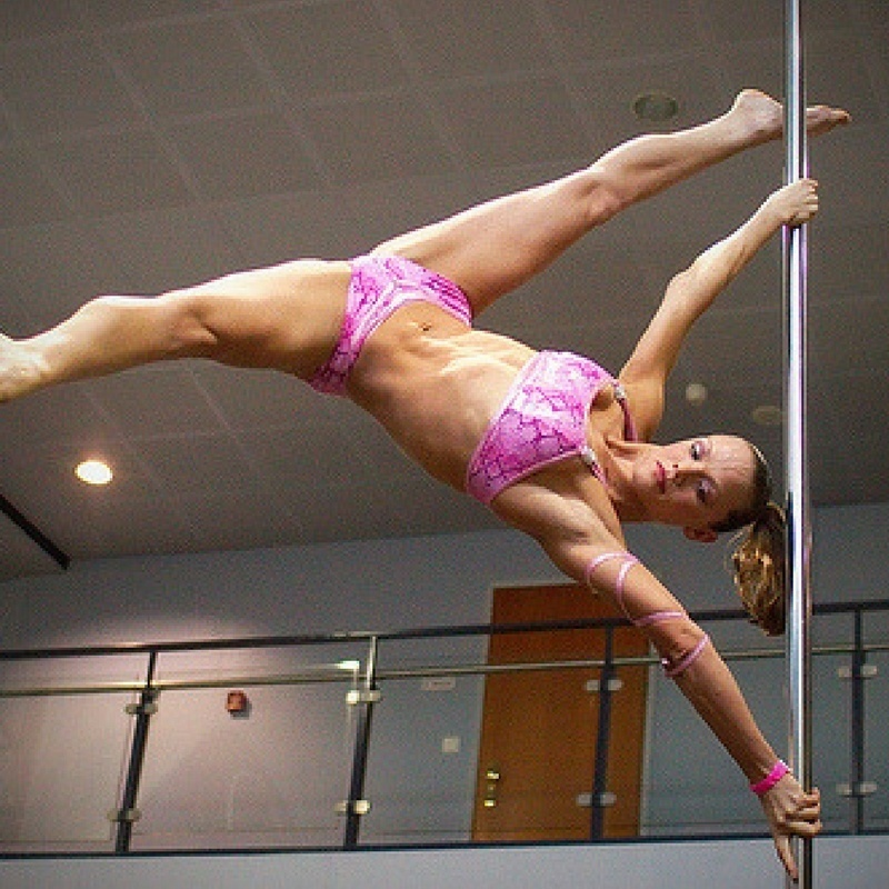 Pole dancer performing an extended butterfly