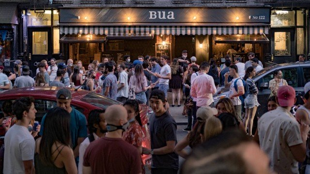 x88461808 people drink outside a bar during the outbreak of the coronavirus disease covid 19 in the e.jpg.pagespeed.ic .GtpXhEx0Cj - Universitários fazem 'festas Covid' com aposta para ver quem pega coronavírus primeiro