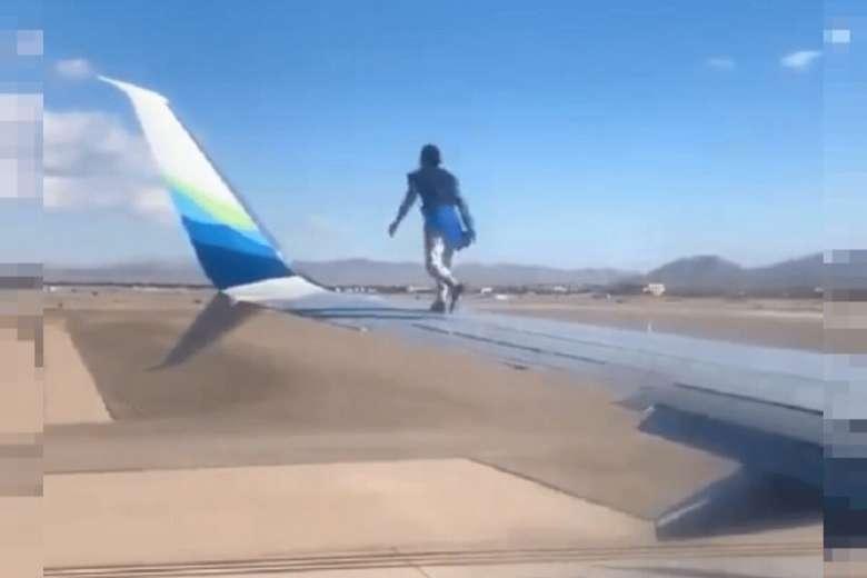 homem no avião - Homem sobe na asa de avião minutos antes da decolagem