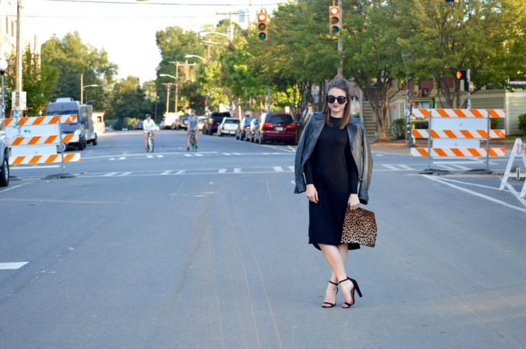 black midi dress and leather jacket and leopard clutch
