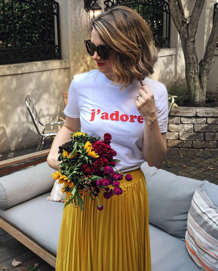 A mustard yellow midi skirt and a graphic tee