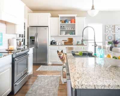 White kitchen with aqua accents, dark island, and granite