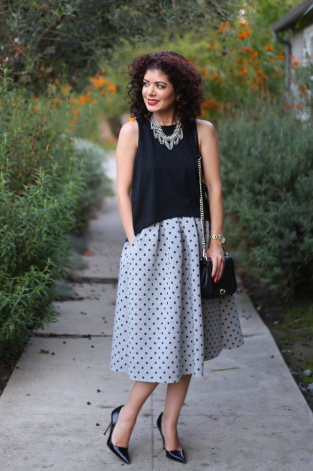 accessories make the outfit with polka dot midi skirt with black heels and black bag