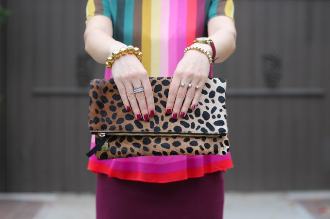 Polished whimsy in multi colored striped shirt and leopard print clutch