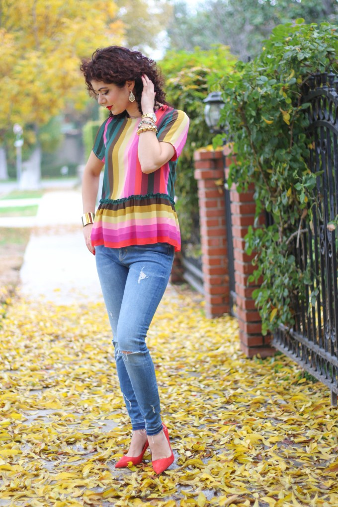 everyday style blogger polished whimsy wearing spring trend colorful rainbow stripes with distressed denim and red pumps