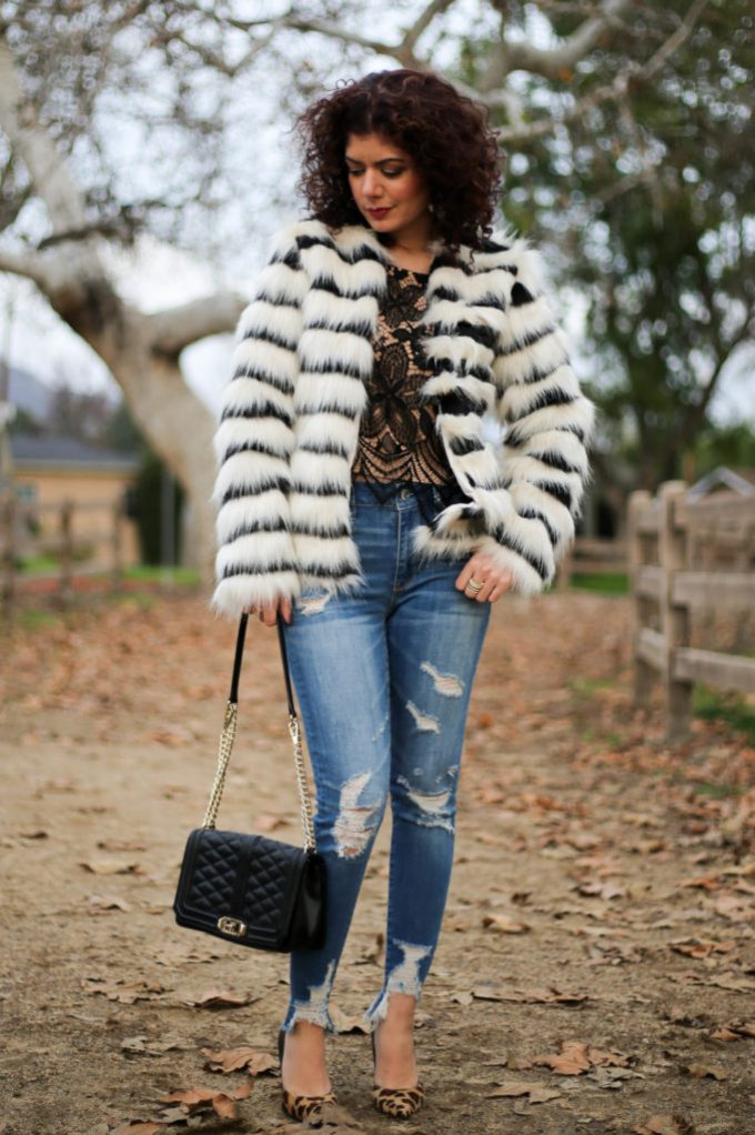 Polished whimsy in striped fur coat with lace top and distressed jeans