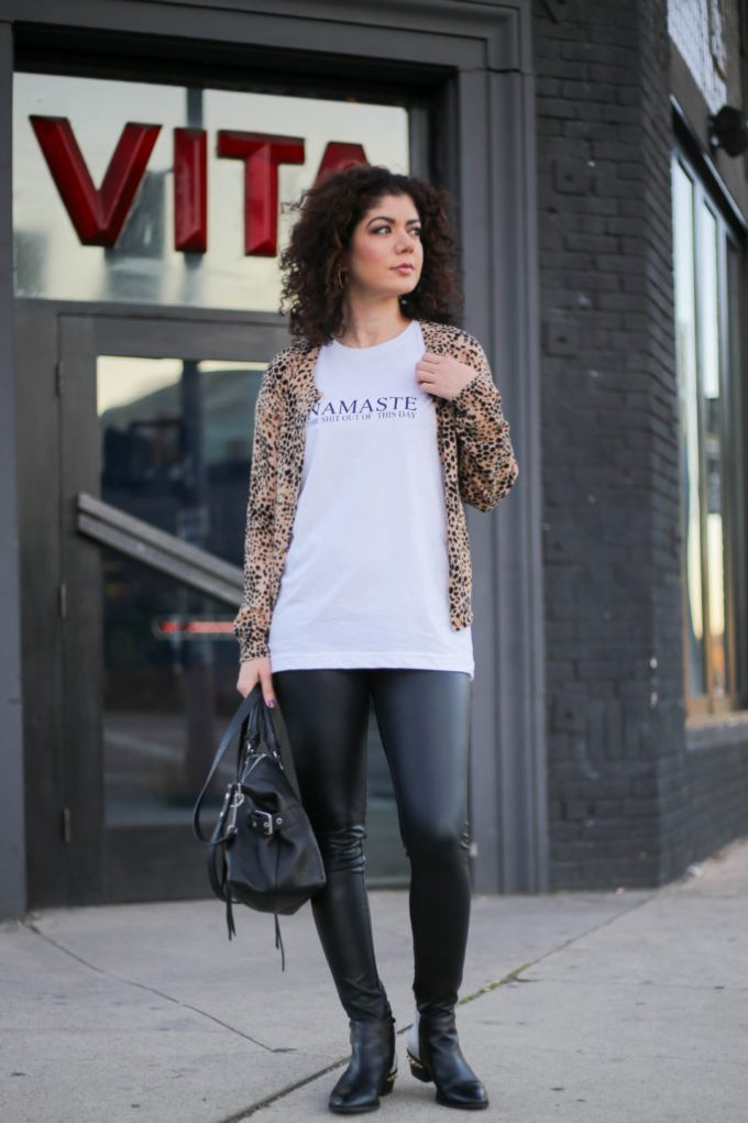 Fashion blogger polished whimsy styling a graphic tee for a casual day with a leather leggings, leopard print cardigan and booties