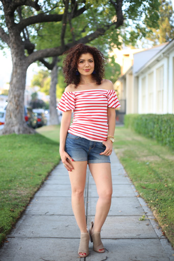 Fourth of July outfit ideas such as a casual look with denim shorts and red striped off the shoulder top
