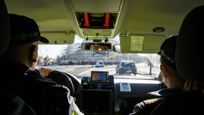 Twee agenten in dienstauto kijken uit op de weg voor hen