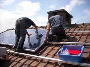 men installing solar panels on roof
