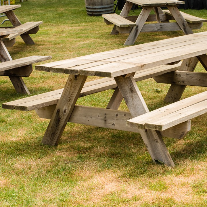 wooden picnic tables on grass