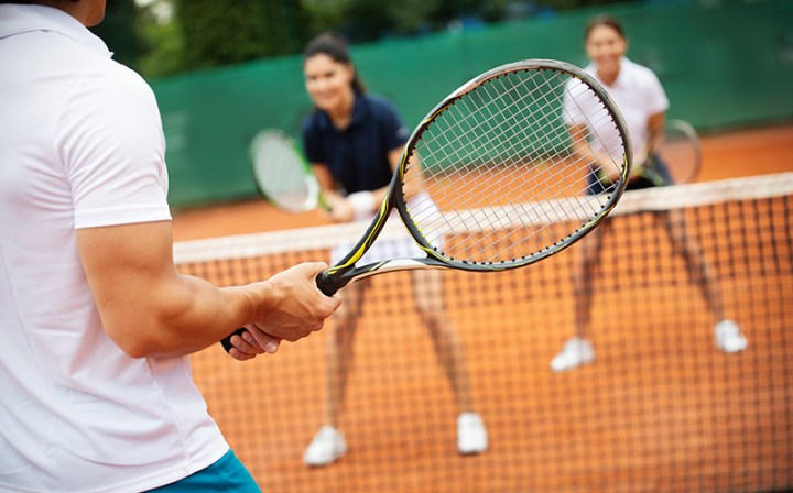 Friends and coworkers playing tennis and learning to play tennis as an outdoor hobby