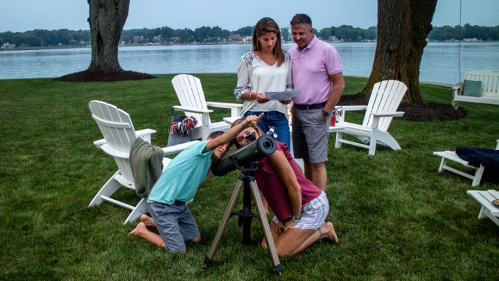 Family stargazing with telescope at dusk with POLYWOOD Adirondack chairs