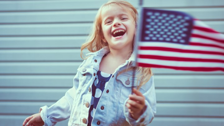 Child holding American flag on July 4th Independence Day at outdoor party