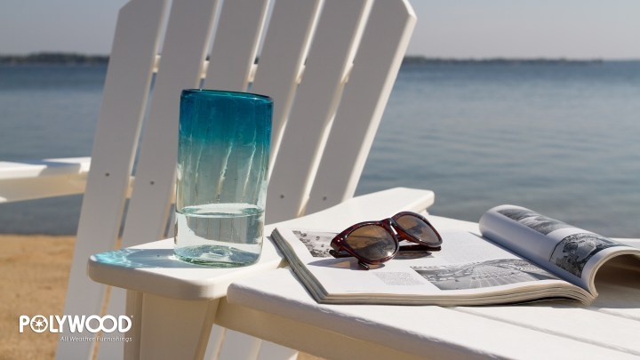 glass of water on adirondack chair on beach