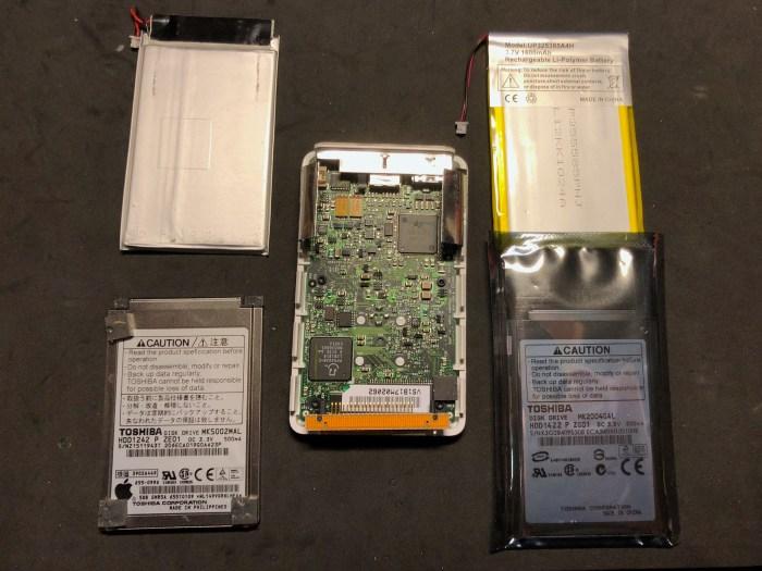 iPod 1G démonté, avec une batterie neuve et un disque dur neuf prêts à être installés.