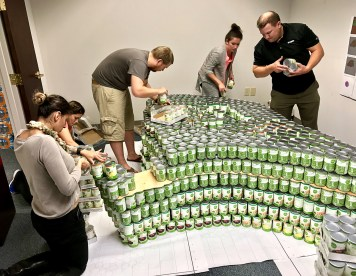 """The Atlanta Canstruction team practices the """"Can Goddess"""" build."""