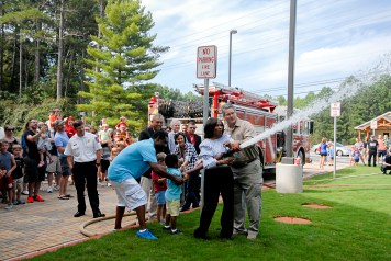 """Deputy County Manager Dr. Jackie McMorris and Director Heaton lead the ceremonial """"uncoupling of the hose""""."""