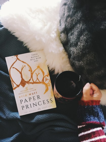 my library book copy of a paper princess lies against a blanket with my cat next to the book and a cup of tea in my hand