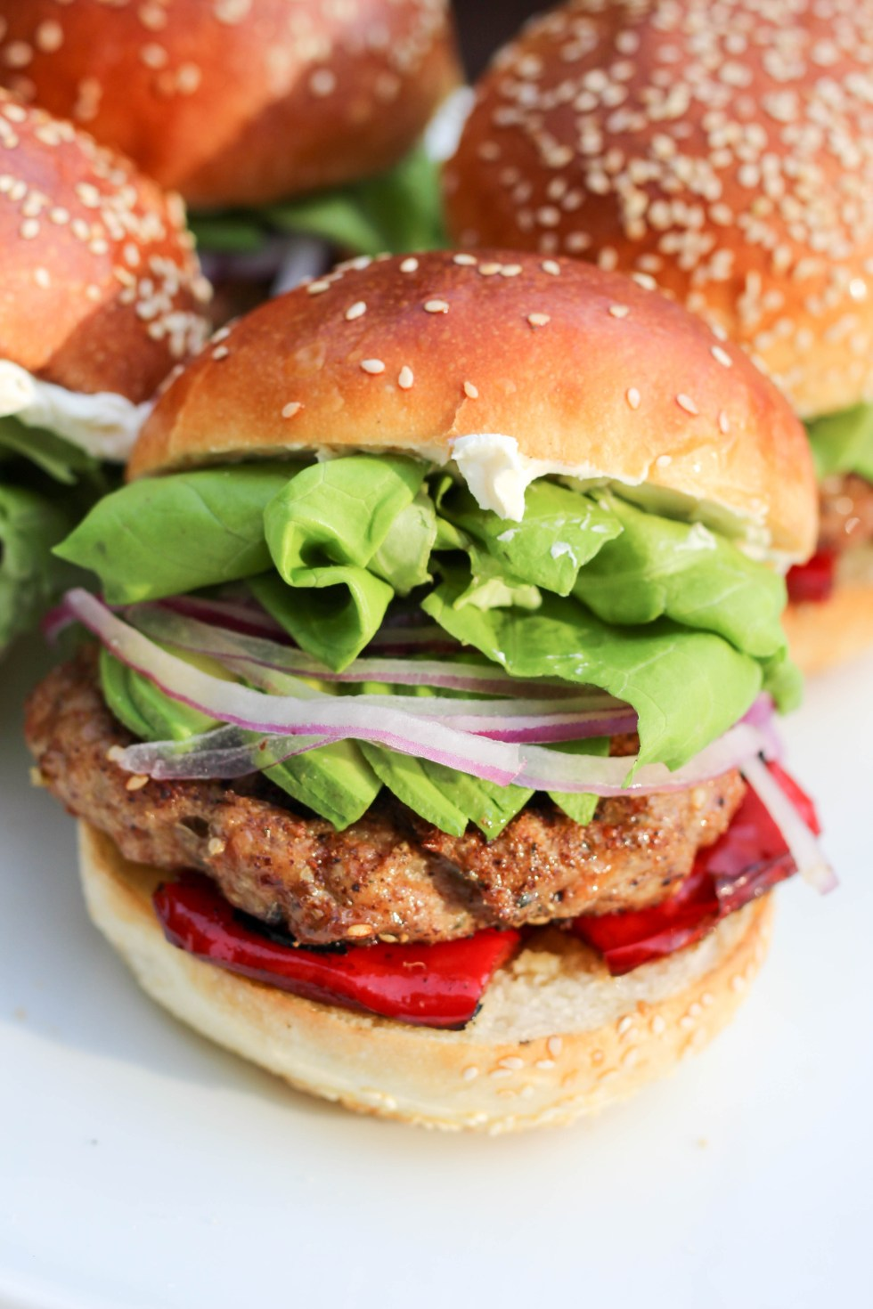 Grill up these za'atar chicken burgers this summer loaded with roasted red peppers and avocado and shmeared with labneh | POP KITCHEN