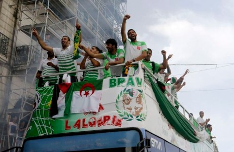 Algeria's soccer players celebrate as they are welcomed by fans in downtown Algiers, after returning from the 2014 World Cup soccer tournament