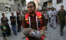 Il cadavere di una bimba di quattro mesi portata via dalle macerie di un palazzo bombardato.
