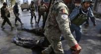 Poliziotti afghani portano via i cadaveri di due talebani dopo uno scontro a fuoco.