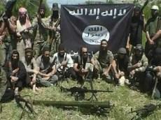 Un commando jihadista posa davanti alla tipica bandiera nera.