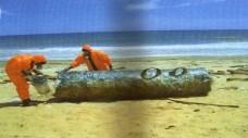 Due tecnici delle Nazioni Unite esaminano un fusto radioattivo su una spiaggia della Somalia centrale.