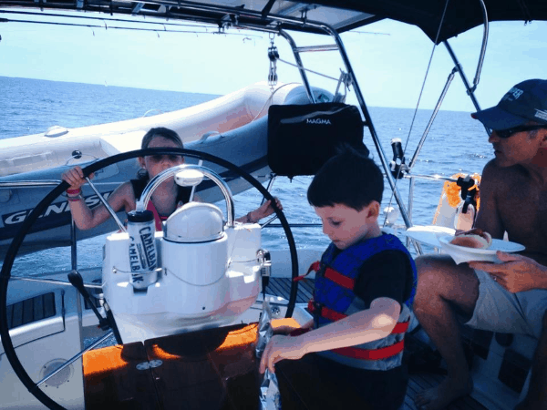 Two young children wearing life jackets and steering the boat, supervised by their dad.