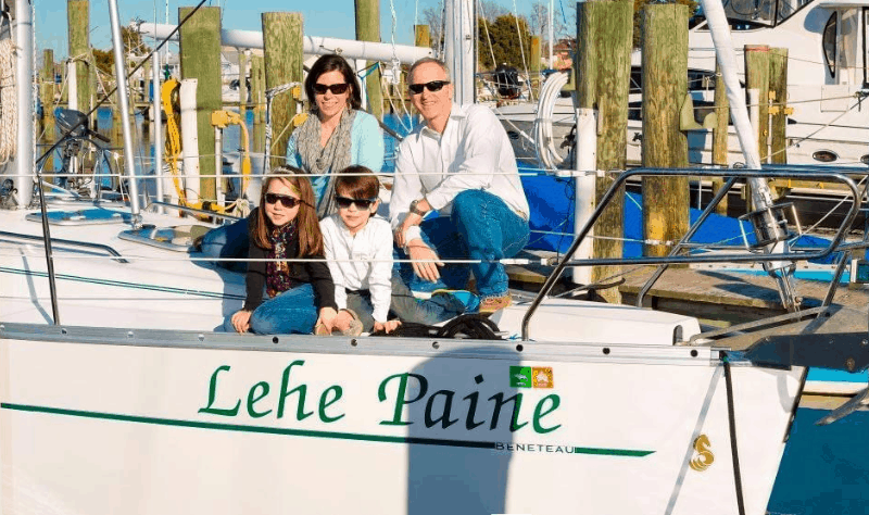 A family of 4 with two young children on the deck of their sailboat, the Lehe Paine.