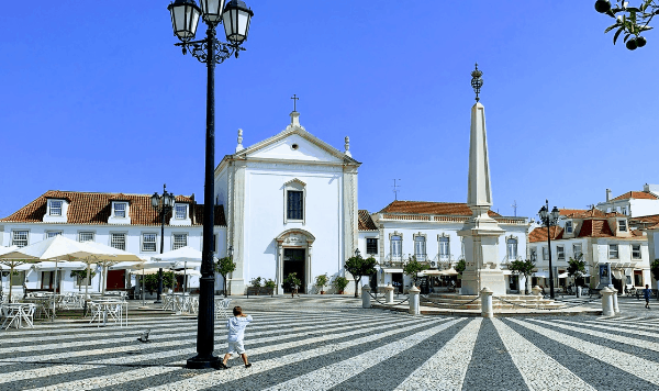 A city square surrounded by wide buildings with an obalisk in the center.