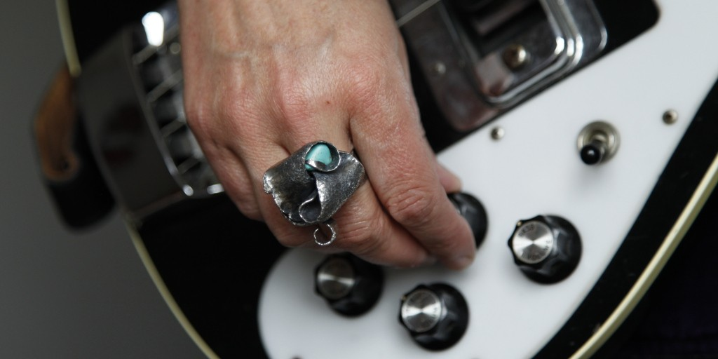 silver and turquoise ring worn by a bass player