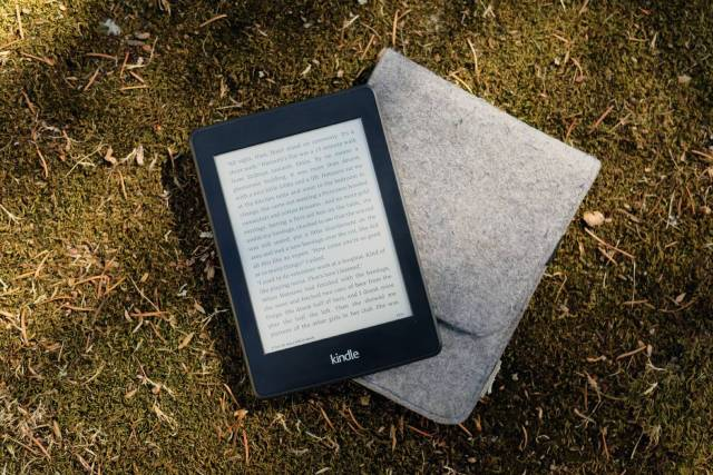 An Amazon Kindle Paperwhite e-reader on a mossy surface. Some consider this the best e-reader.