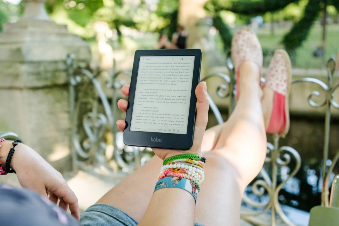 A person holding a Kobo Clara HD while sitting outside with their feet up.