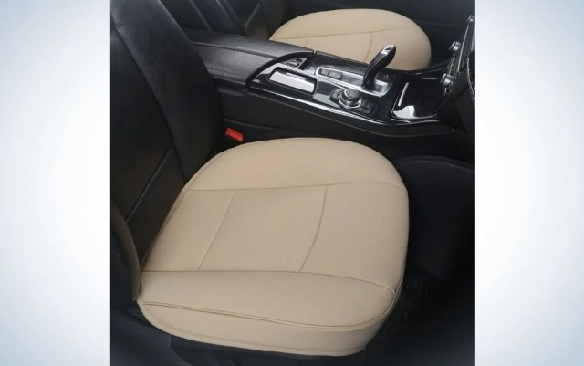 Inside a black car with a beige cover in the passenger and driver seats.
