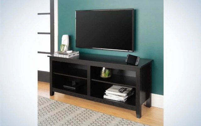 Black television standing on a blue wall with a black wooden Tv stand with books and magazines in it.
