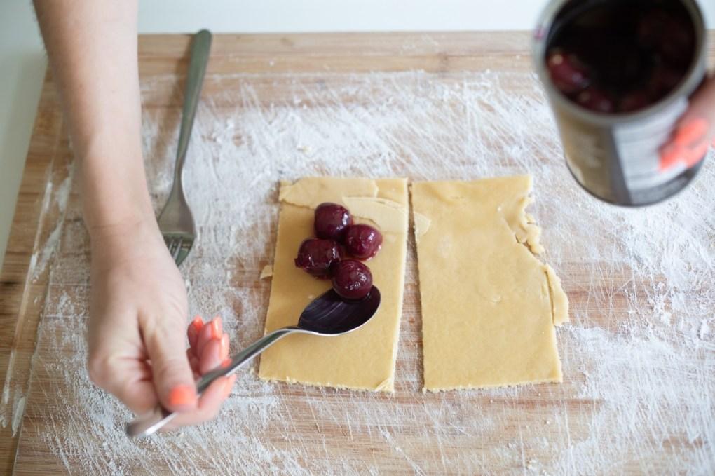 spoon in cherries to make cherry hand pies