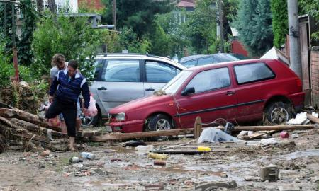 People walk on the street after heavy floods in Cento near Skopje, Macedonia, August 7, 2016. REUTERS/Stringer