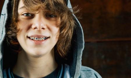 Smiling teen boy it braces in hoodie, Seattle, WA