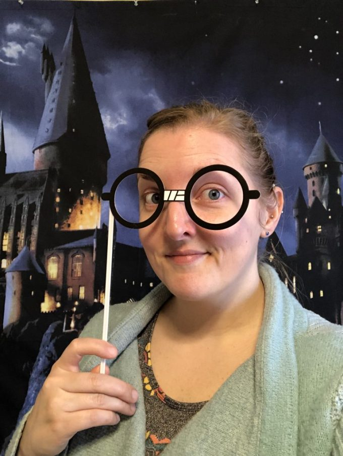Me wearing Harry Potter-style glasses, standing in front of a backdrop of Hogwarts at night