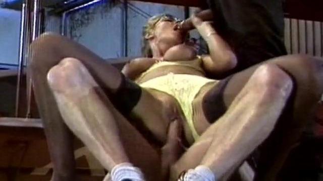 Partouze sur une femme mûre dans un hangar d'avions