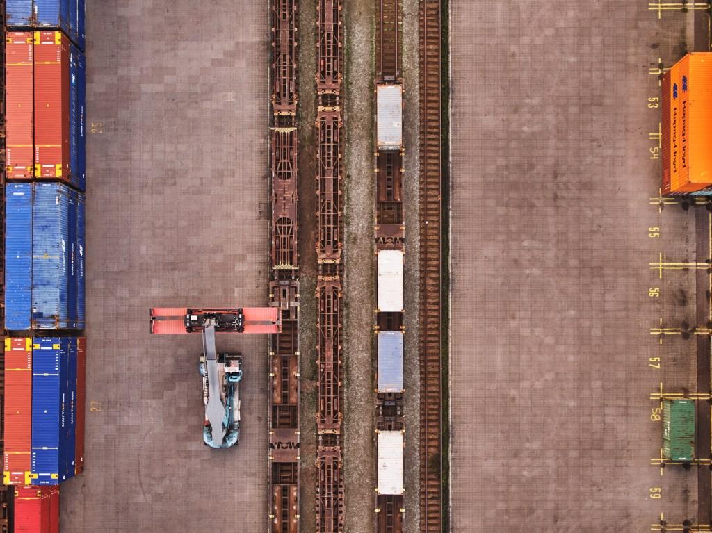 Truck lastar container på järnvägspendel.