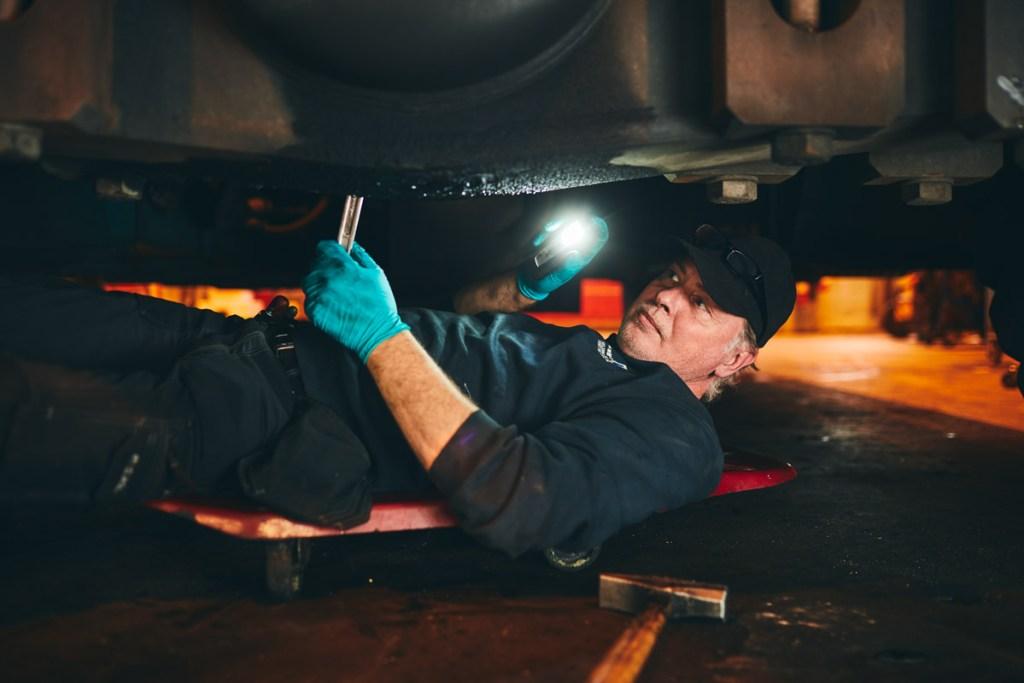 En medarbetare på verkstaden ligger under en bil och håller in en skiftnyckel