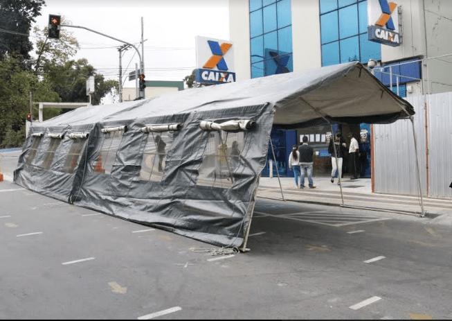 As tendas foram colocadas na rua da agência, onde já havia demarcação no asfalto para manter o distanciamento na fila.