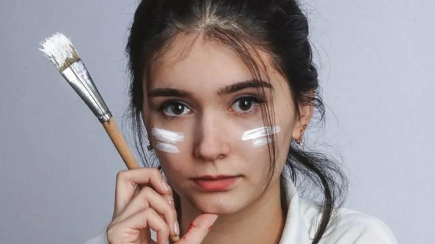 Influências. Jovem com pincel na mão pintando o rosto