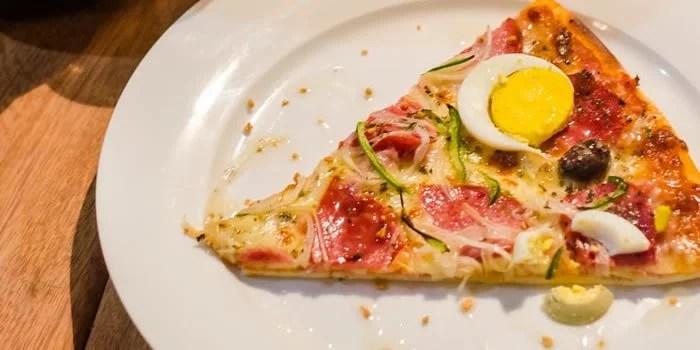 Fatia de pizza com calabresa e ovos cozidos.