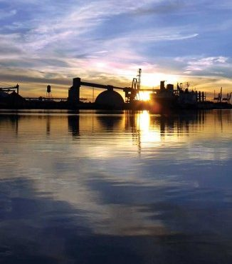 Water view with the sun setting behind Port of Stockton