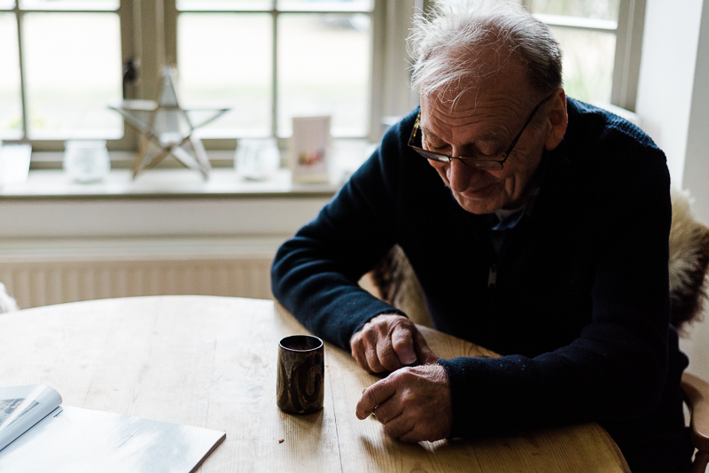 grandfather sitting at pine table drinking coffee