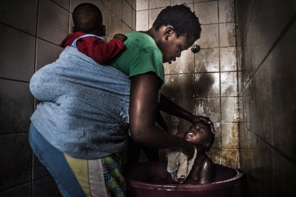 Busi is washing her children in one of the shower booth in the building. There is just cold water, and many of the toilets in the room don't work, so the place stinks of human feces. Johannesburg 2015